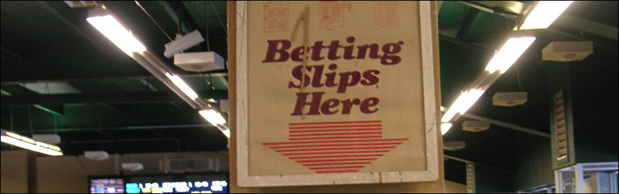 """Sign at a track that reads """"Betting Slips Here"""""""